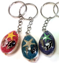 Seastar and colored sand in resin domed cowrie shell key rings